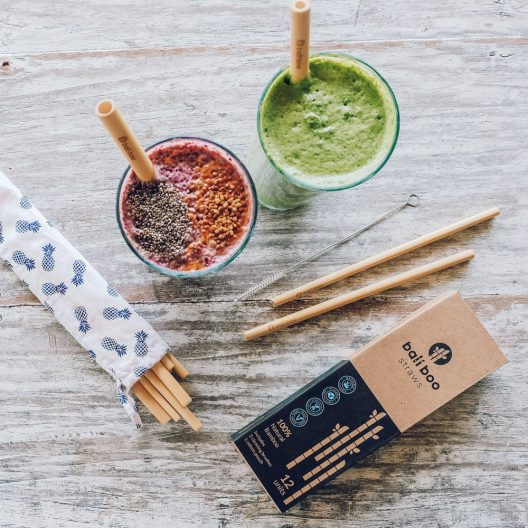 pack of 12 bamboo straws with cleaning brush and pouch next to two smoothies with bamboo straws