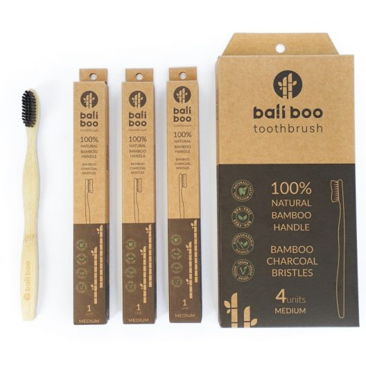 bamboo toothbrush next to individual packaging and pack of 4 bamboo toothbrushes