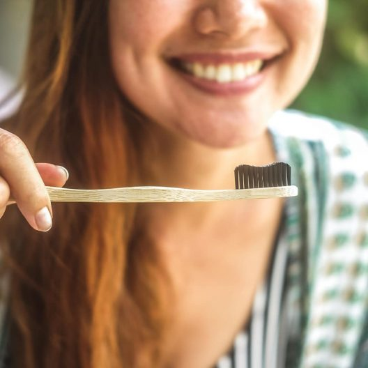 girl holding a bamboo toothbrush with activated bamboo charcoal bristles